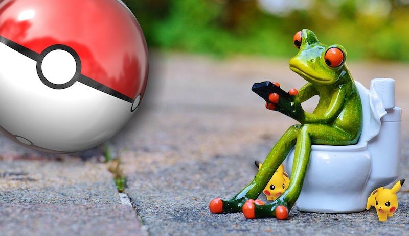 Frosch sitzt auf einer Toilette beim Handy Spiele